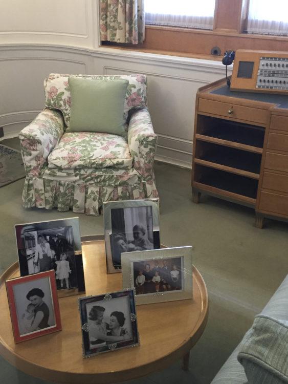 Laivan sisätiloja, etualalla pöydällä kuninkaallisen perheen kuvia, takana nojatuoli.