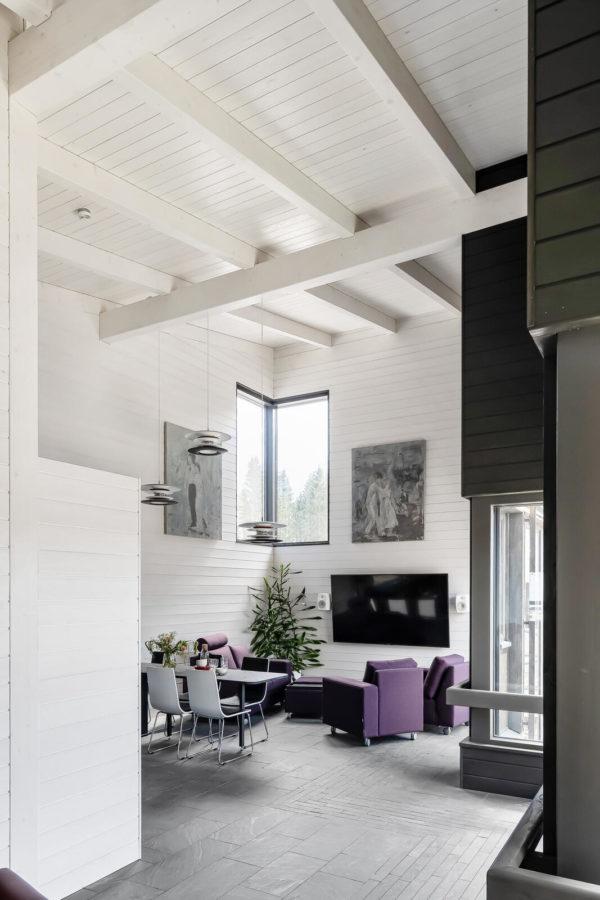 Valkoinen olohuone on korkea, huonekalut ovat violetteja tai valkoisia.