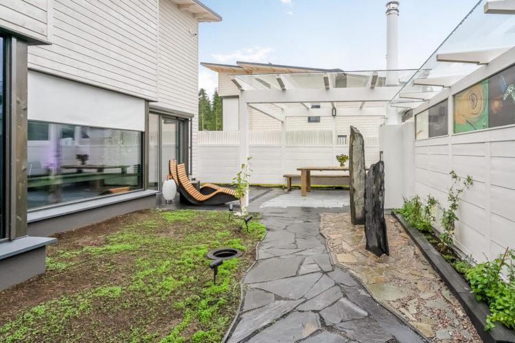 Molemmilla taloilla on yhteinen oleskelupiha puisine lepotuoleineen.