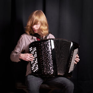 Taiteilija Joose Ojala haitari sylissään soittamassa.