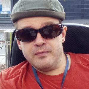 Riku Ryynänen punaisessa t-paidassa myssy päässä ja mustat lasit silmillä.