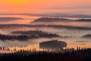 Jarmo Mannisen maisema on värjäytynyt oranssiksi, kuvassa on saaria, vettä ja puita.