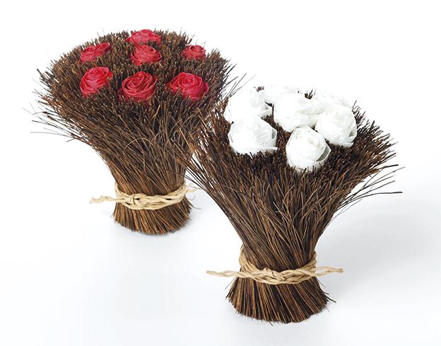 Punaisia ja valkoisia paperiruusuja oksakimpun päällä, toisessa kuvassa rottinkivalaisimia kauniisti aseteltuina