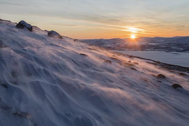 Aurinko nousee tunturin takaa, edessä toisen tunturin kylkeä.