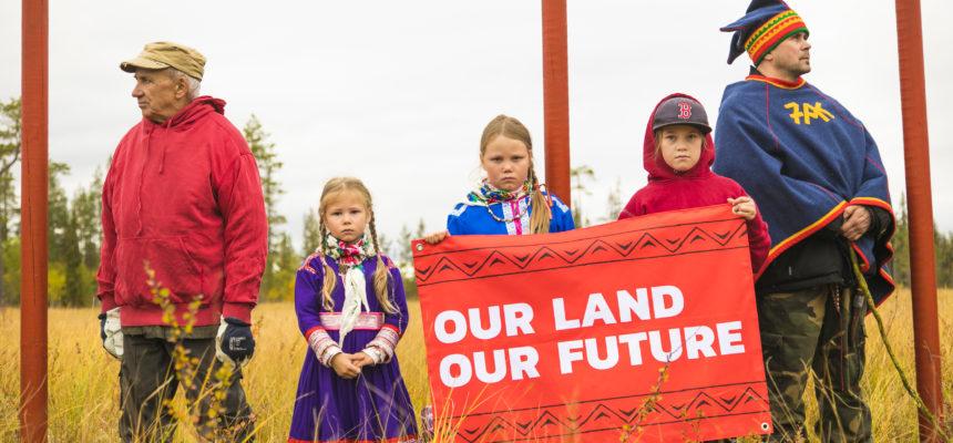 Punaisessa kolmen lapsen pitämässä julisteessa lukee Our land Our future. Oikealla puolella seisoo mies lapinpuvussa, vasemmalla vanha mies punainen anorakki päällään.