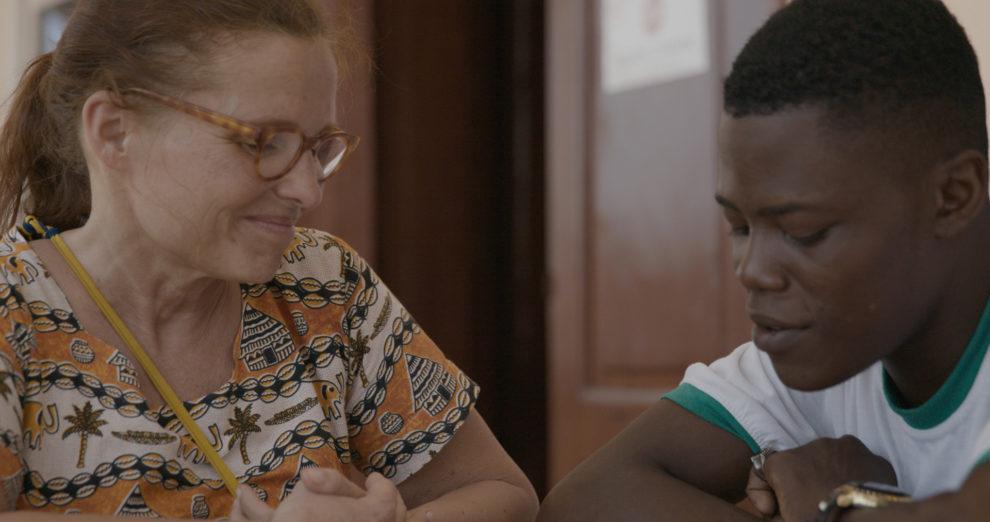 Missä tiet kohtaavat elokuvasta otetussa kuvassa on nuori tummaihoinen poika ja vaaliea silmälasipäinen nainen.