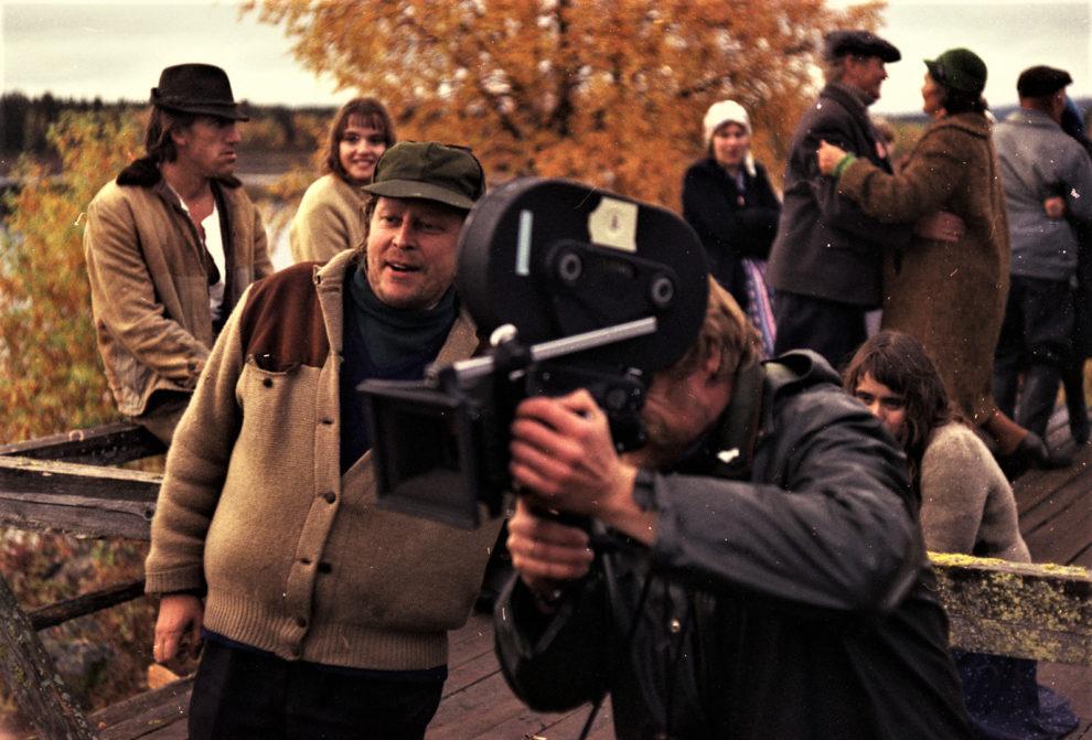 Rauni Mollberg ohjaa kuvaajaa, jolla on iso filmikamera harteillaan, taustalla on elokuvan avustajia.