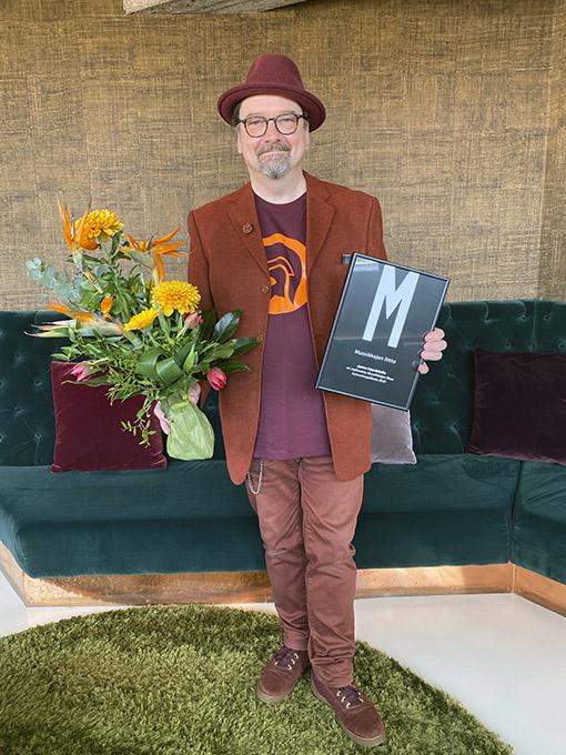 Janne haavisto kunniakirjan ja kukkien kanssa.