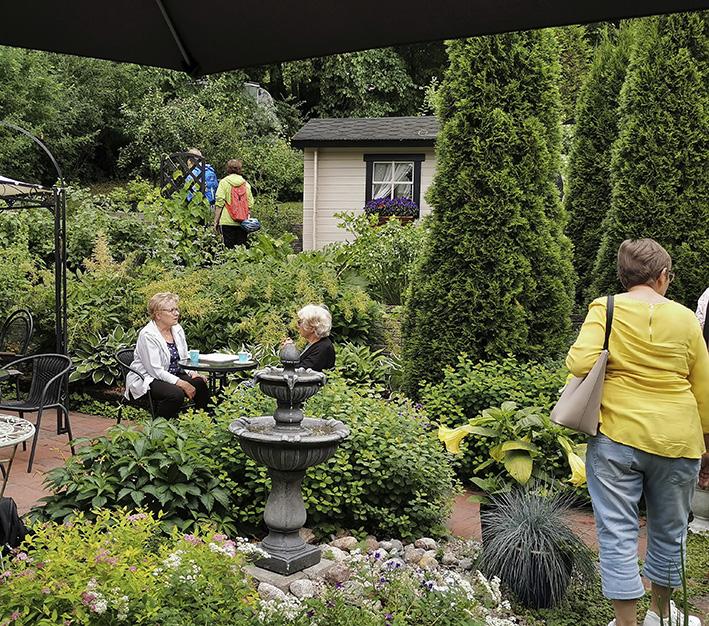 Esimerkkipuutarhassa on sypressejä ja kukkia ja vieraita.