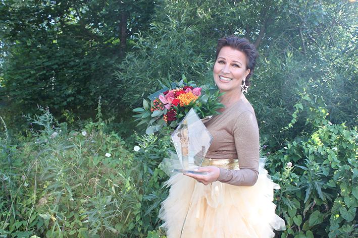 Arja Koriseva tyllihameessa kukkalaite sylissään Suomen luonnossa.