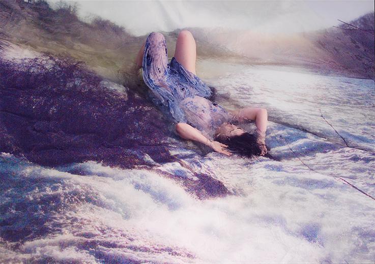 Nainen makaa rantakalliolla veden huuhdottavana ihanan herkässä kuvassa.