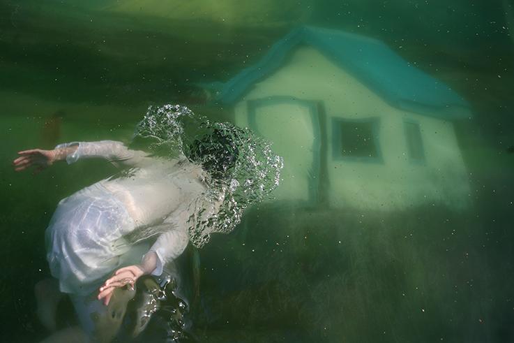 Sukeltava nainen kohtaa vihreässä vedessä unenomaisen talon.