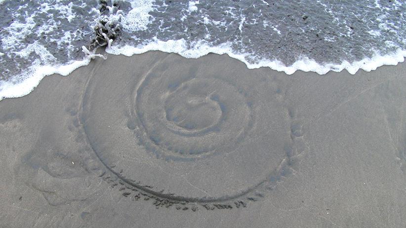 Vesi on muotoillut rantahiekkaan ympyröitä.